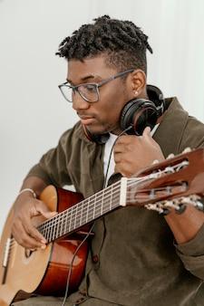 Hübscher männlicher musiker zu hause, der gitarre spielt und kopfhörer benutzt