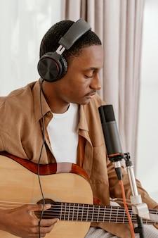 Hübscher männlicher musiker zu hause, der gitarre spielt