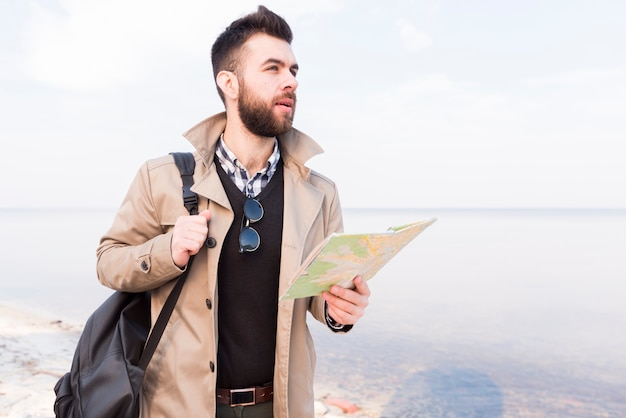 Hübscher männlicher reisender, der nahe dem meer hält die karte in der hand schaut weg steht