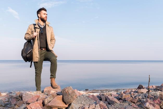 Hübscher männlicher reisender, der vor dem meer hält handtasche auf der schulter weg schaut steht