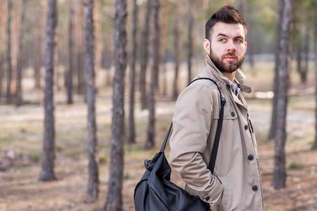 Hübscher männlicher reisender mit rucksack auf seiner schulter, die weg schaut