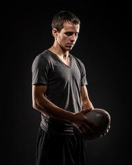 Hübscher männlicher rugbyspieler, der ball hält