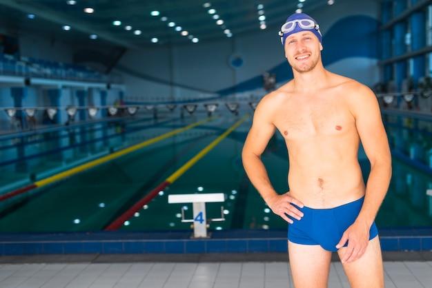 Hübscher männlicher schwimmer, der vor swimmingpool aufwirft