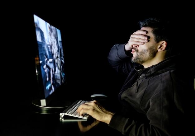 Hübscher männlicher spieler, der computervideospiel spielt
