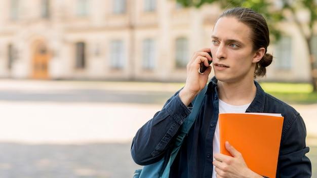 Hübscher männlicher student, der am telefon spricht