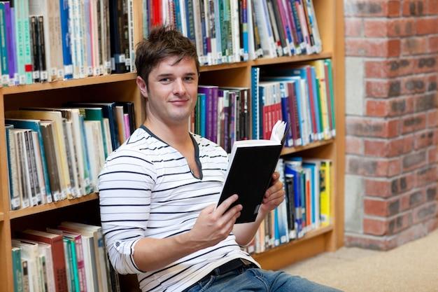 Hübscher männlicher student, der ein buch sitzt auf dem boden liest