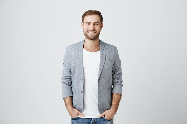 Hübscher männlicher unternehmer, der fröhlich lächelt