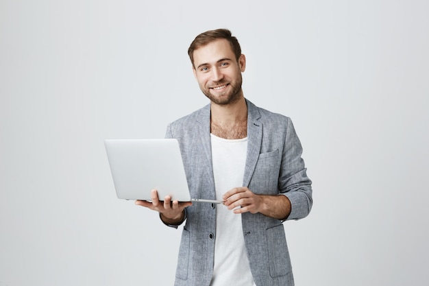 Hübscher männlicher unternehmer, der laptop verwendet