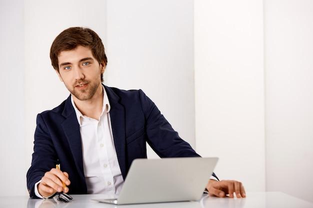 Hübscher männlicher unternehmer im anzug sitzen am schreibtisch mit laptop, schauen erfreut