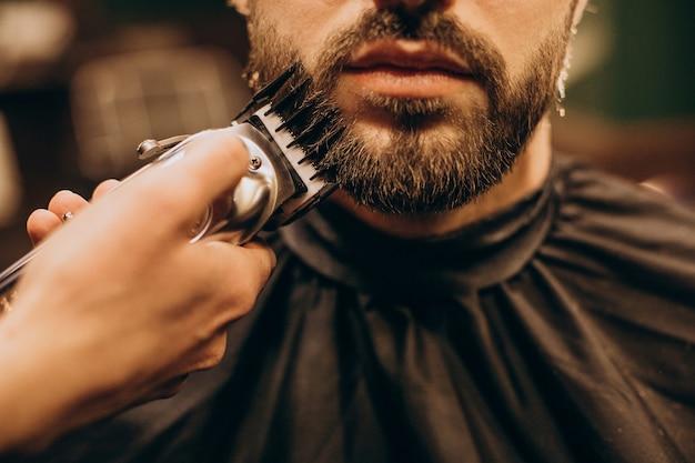 Hübscher mann am friseursalon, der bart rasiert