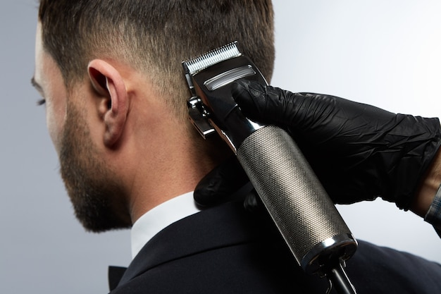 Hübscher mann am friseursalon, der blak anzug trägt, männerhände, die einen haarschnitt mit trimmer für mann mit schwarzen haaren am studiohintergrund machen.