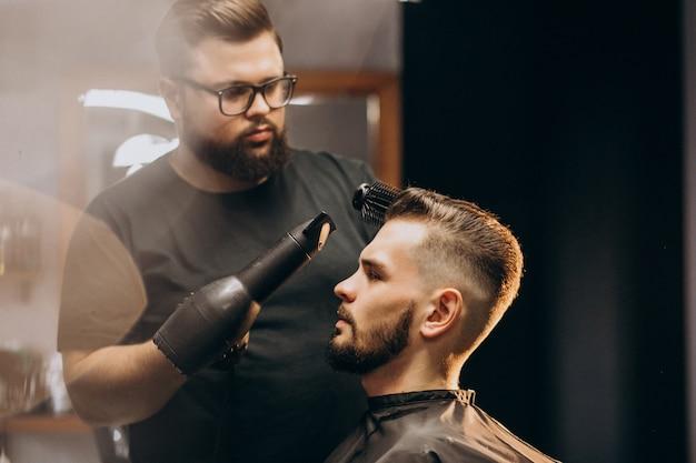 Hübscher mann an einem friseurladen, der haare stylt