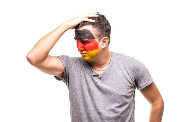 Hübscher mann anhänger fan der deutschen nationalmannschaft gemalt flagge gesicht bekommen unglücklich traurig frustriert emotionen in eine kamera. fans emotionen.