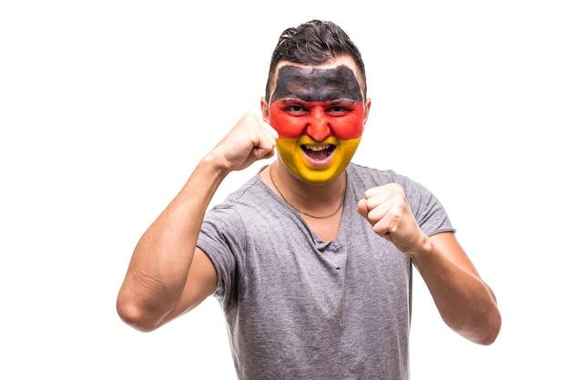 Hübscher mann anhänger fan der deutschen nationalmannschaft mit gemaltem flaggengesicht erhalten glücklichen sieg, der in eine kamera schreit. fans emotionen.