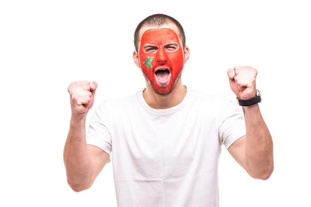 Hübscher mann-anhänger-fan der gemalten flaggengesicht der marokkanischen nationalmannschaft erhalten glücklichen sieg, der in eine kamera schreit. fans emotionen.