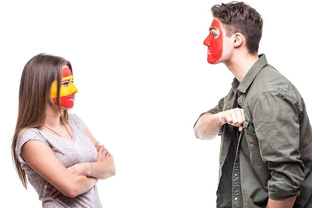 Hübscher mann-anhänger-fan der portugiesischen nationalmannschaft gemaltes flaggengesicht demonstrieren loyalität gegenüber weiblichem anhänger-fan der spanischen nationalmannschaft. fans emotionen.