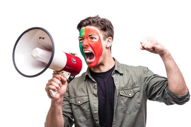 Hübscher mann anhänger treuer fan der portugiesischen nationalmannschaft gemalt flagge gesicht erhalten glücklichen sieg schreien in megaphon mit spitzen hand. fans emotionen.