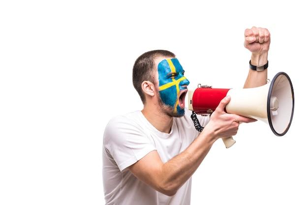 Hübscher mann anhänger treuer fan der schwedischen nationalmannschaft mit gemaltem flaggengesicht erhalten glücklichen sieg, der mit spitzer hand in megaphon schreit. fans emotionen.