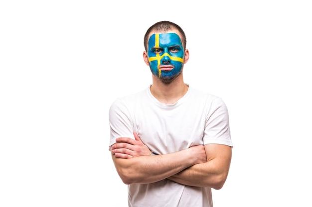 Hübscher mann-anhänger treuer fan der schwedischen nationalmannschaft mit gemaltem flaggengesicht lokalisiert auf weiß. fans emotionen.