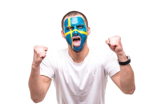 Hübscher mann-anhängerfan der schwedischen nationalmannschaft mit gemaltem flaggengesicht erhalten glücklichen sieg, der in eine kamera schreit. fans emotionen.