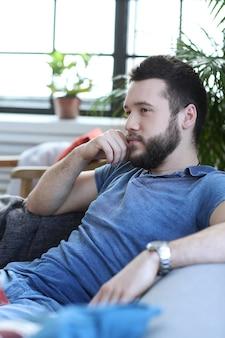Hübscher mann auf dem sofa