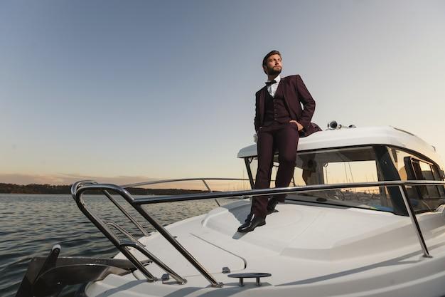 Hübscher mann auf einer regatta. junger mann, der auf der yacht im meer bei sonnenuntergang steht