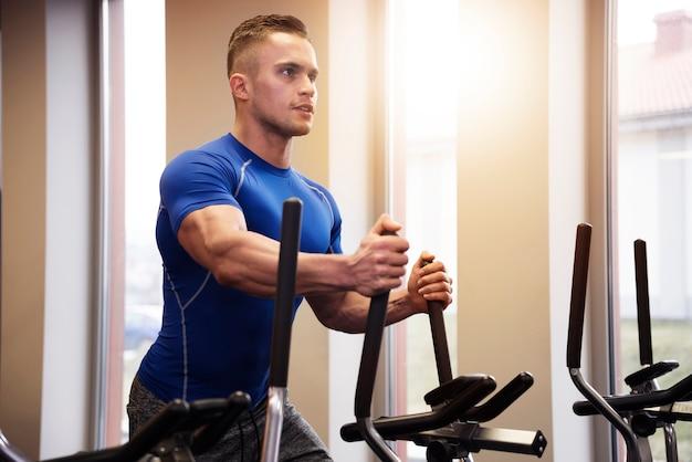 Hübscher mann auf elliptischem trainer