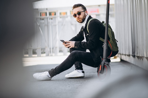 Hübscher mann auf roller, der online am telefon einkauft