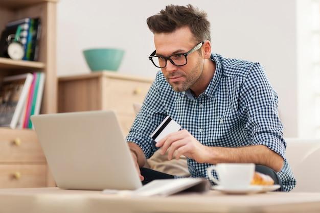 Hübscher mann beim online-einkauf