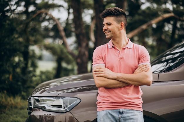 Hübscher mann, der an seinem auto im wald steht