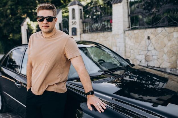 Hübscher mann, der an seinem auto steht