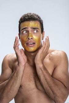Hübscher mann, der angst hat, sein gesicht mit einer maske darauf zu berühren