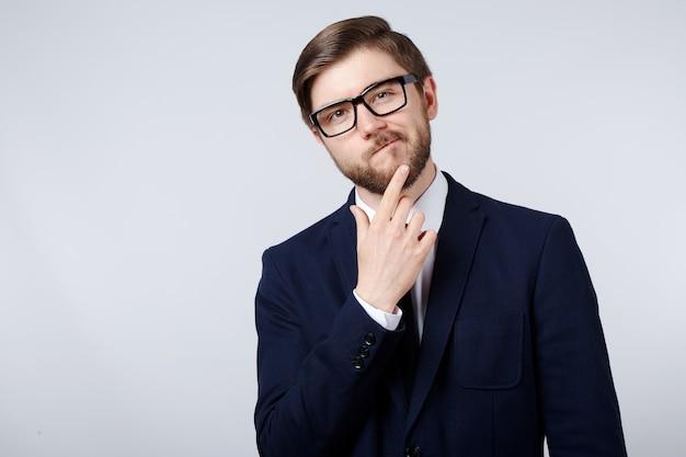 Hübscher mann, der anzug- und brillenwanddenken, geschäftskonzept, kopienraum, porträt trägt.