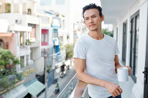 Hübscher mann, der auf balkon steht