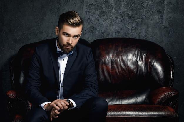 Hübscher mann, der auf dem ledersofa sitzt