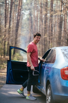 Hübscher mann, der auf der straße nahe geöffneter tür seines autos steht.
