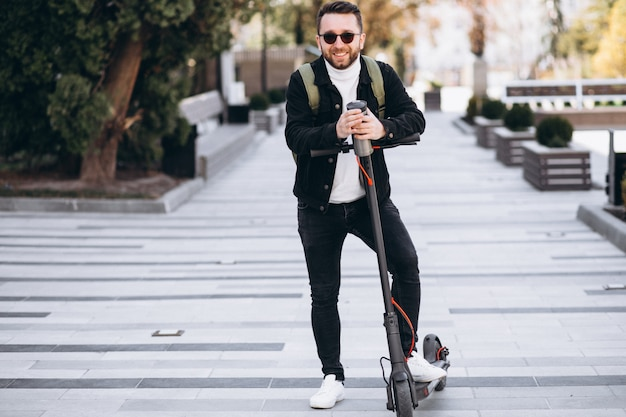 Hübscher mann, der auf roller reitet und kaffee von der thermoskanne trinkt