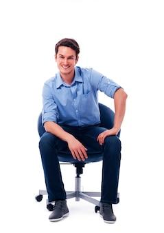 Hübscher mann, der auf stuhl sitzt