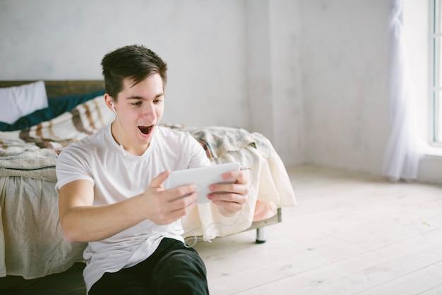 Hübscher mann, der auf tablette surft. kerl spricht mit freunden, videokonferenz, skype, tablet. der junge student blättert in sozialen netzwerken
