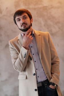 Hübscher mann, der beige mantel trägt