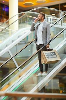 Hübscher mann, der beim einkaufen per telefon spricht