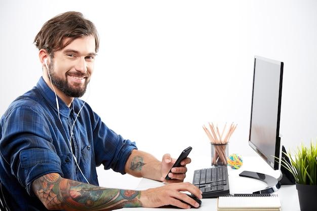 Hübscher mann, der blaues hemd trägt, das mit laptop sitzt und zur musik, freiberufliches konzept, porträt, online-job, entspannung auflistet.