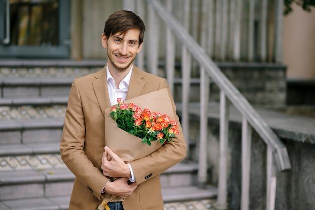 Hübscher mann, der blumenstrauß von rosen hält, lächelt und zeigt zähne