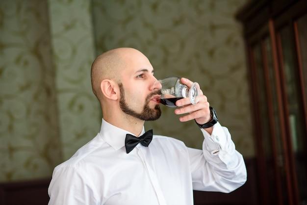 Hübscher mann, der cognac im restaurant trinkt