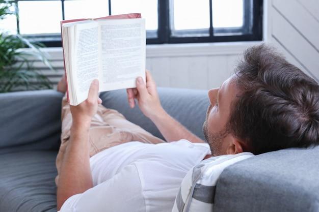 Hübscher mann, der ein buch im sofa liest
