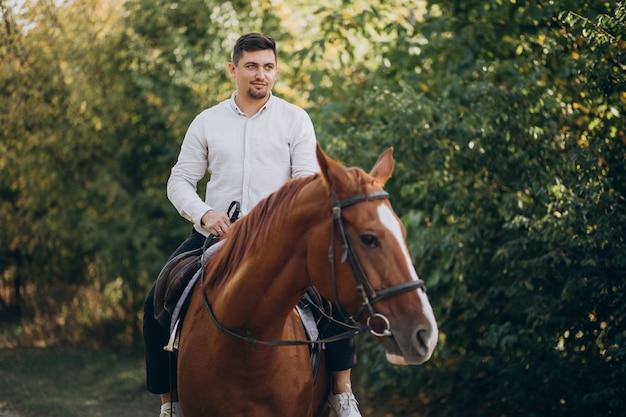 Hübscher mann, der ein pferd im wald reitet