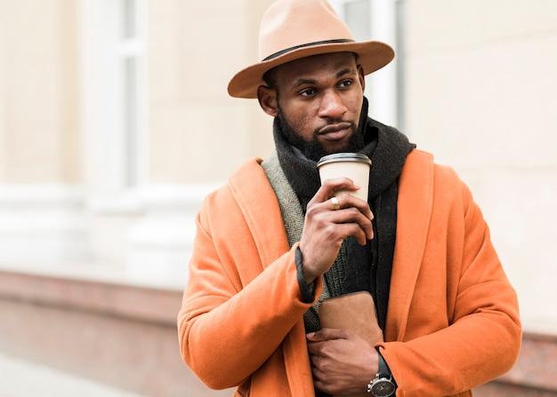 Hübscher mann, der eine tasse kaffee hält