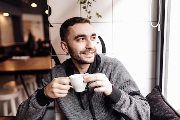 Hübscher mann, der eine tasse kaffee im café trinkt