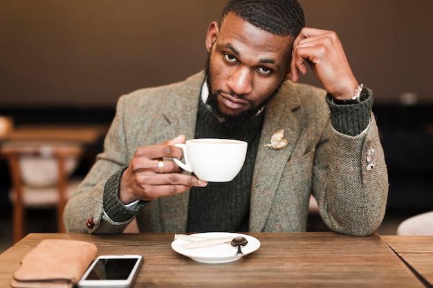 Hübscher mann, der eine tasse mit kaffee beim aufschauen hält