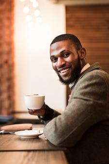 Hübscher mann, der eine tasse mit kaffee in einer kneipe hält